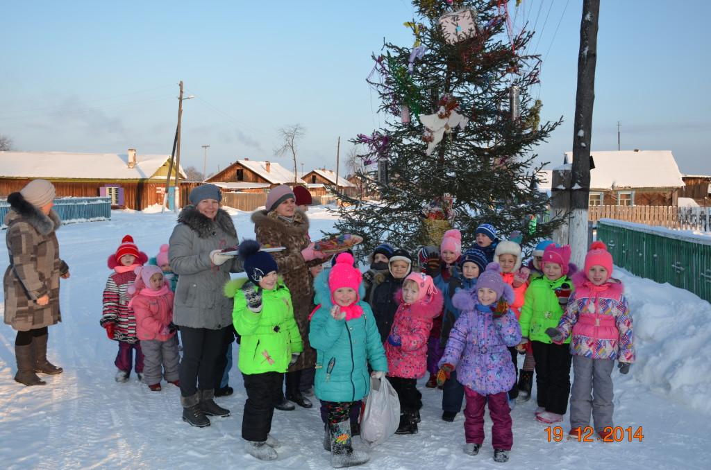 воспитатели детского сада с детьми украшают  новогоднюю елку с.Мирный